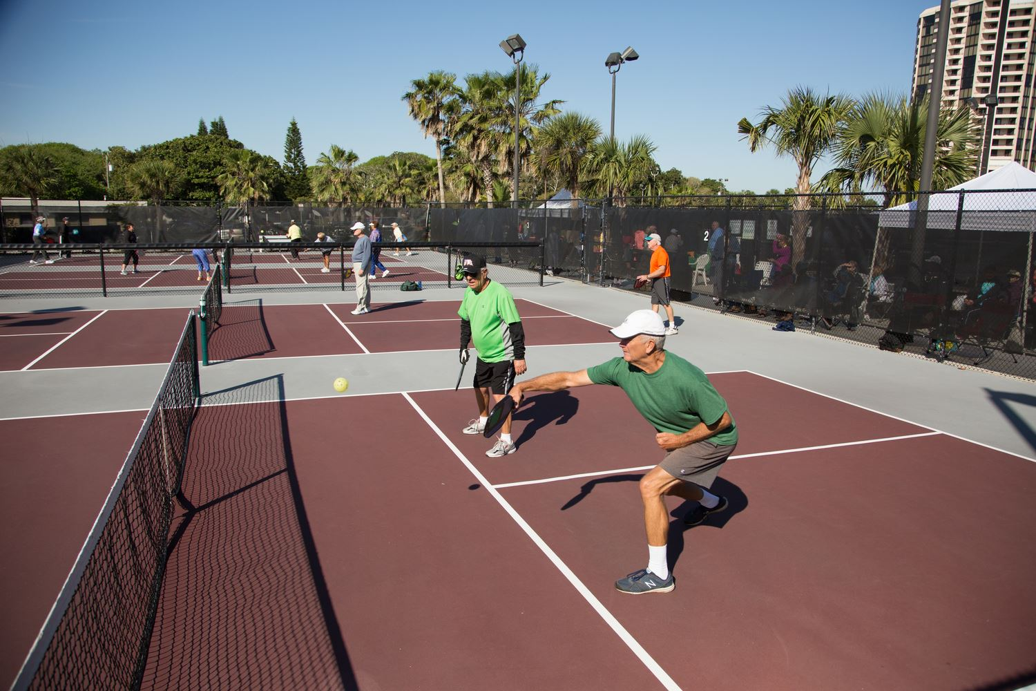 Two Men Playing Pickleball in Green T-Shirts