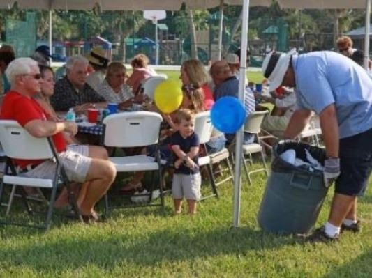 Guests seated at a table under a canopy during a city cookout for residents