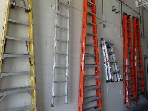 Six ladders of different sizes and colors, neatly hanging in the city Public Works building