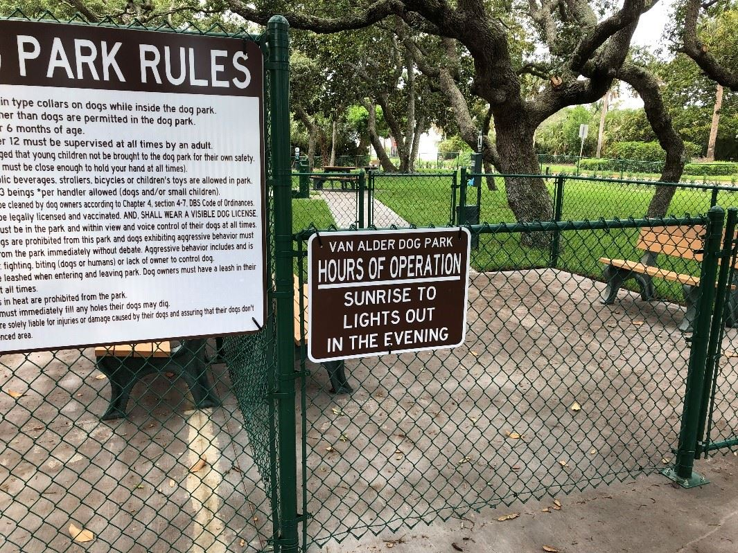 Fence of a Dog Park Containing a list of Rule and Hours of Operation