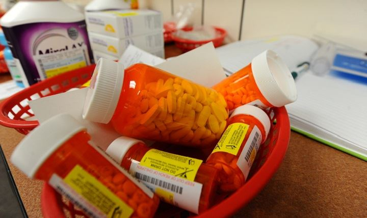 Several bottles of pills in a basket along with other medication
